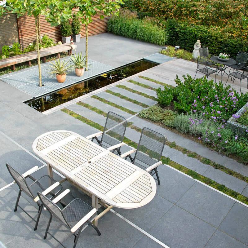 Voorbeeld strakke moderne tuin met tegels en beplanting