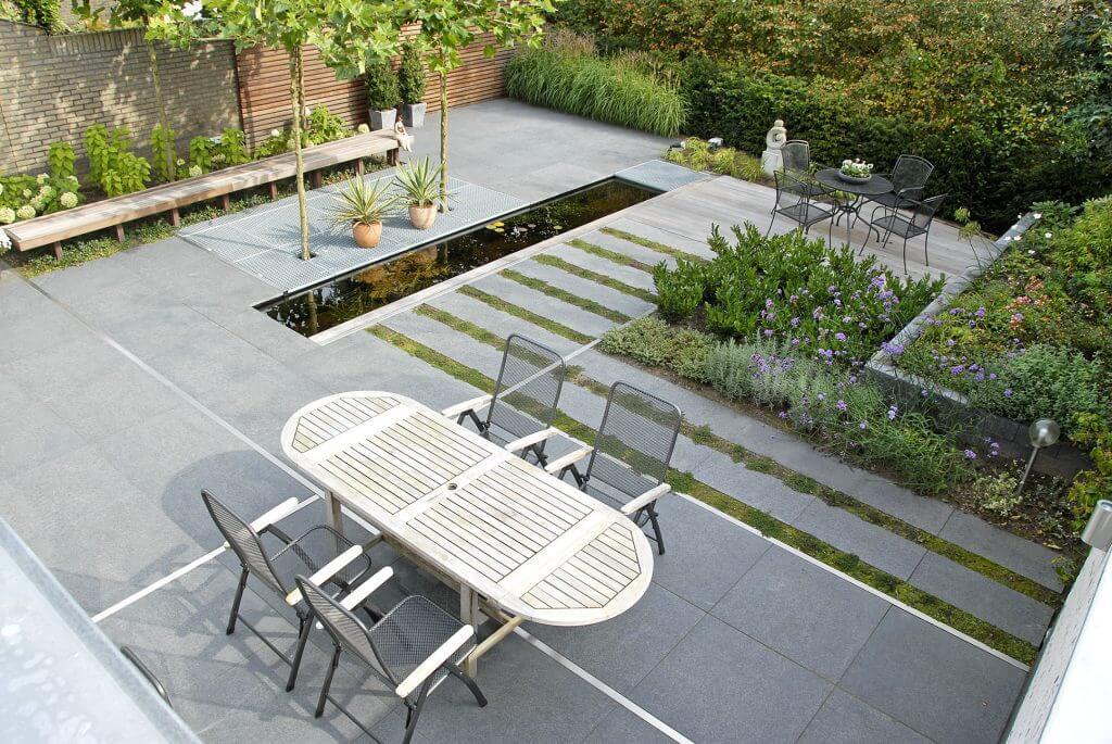 Strakke moderne tuin met grote tegels en lange smalle vijver.