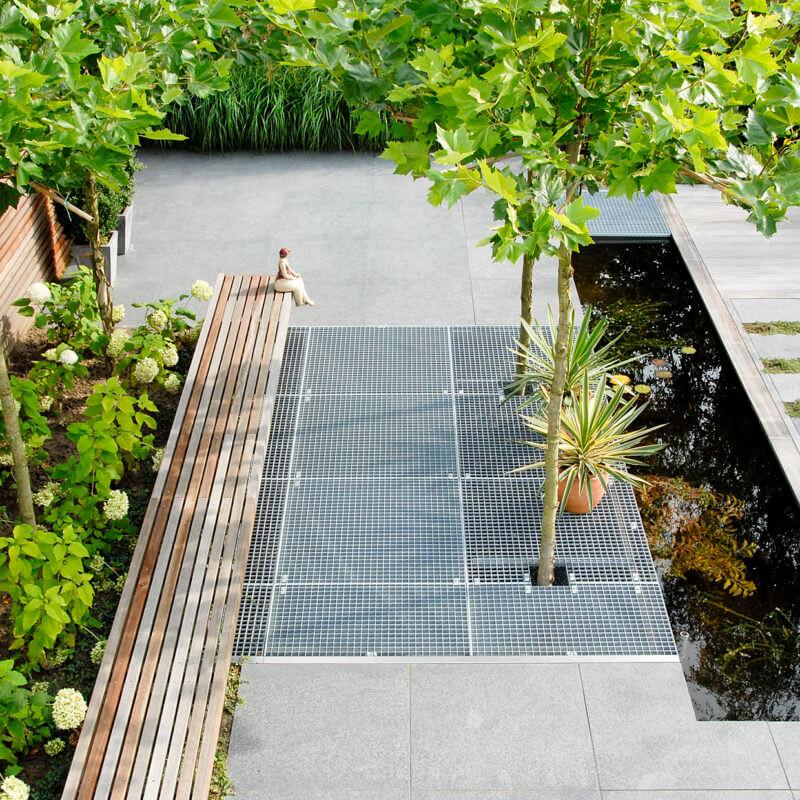 Strakke moderne tuin met bordesroosters en dakplatanen